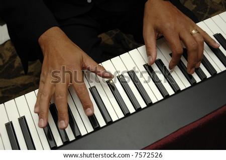 fingers play across a keyboard - stock photo