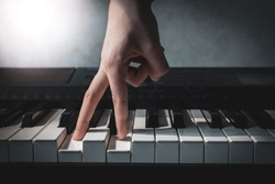 fingers press piano keys close-up, hand of a composer or musician plays a synthesizer