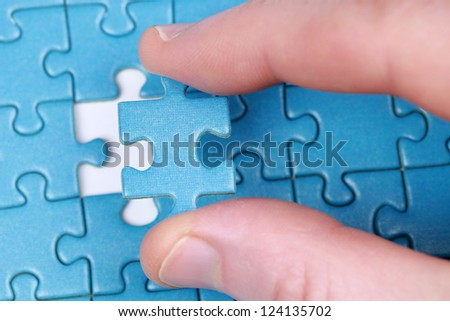 Fingers putting the last piece of puzzle in place