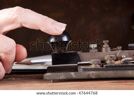 Fingers tapping morse code on an antique telegraph