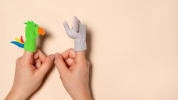 Fingers toys made of fabric on the hands on a beige background. Fingers Theatre. Two arm with toys animals elephant and parrot.