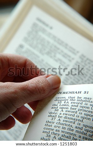 fingers turning pages of the Bible