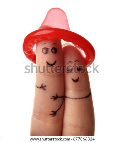 Fingers under condom. Safe sex concept #677866324