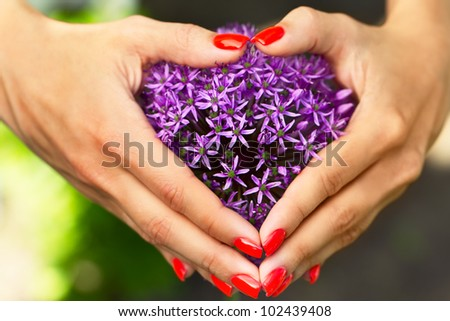 Fingers with red nails are composed the shape of heart