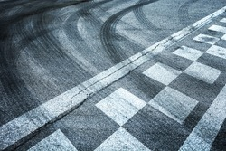 Finish and start pattern line racing on the asphalt road background with crossing of tires tracks.