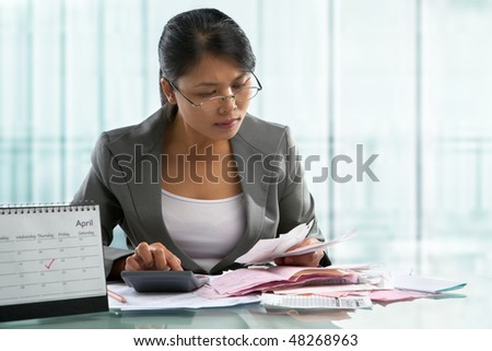 Finishing calculation for tax form on April 15 concept, with calendar in front