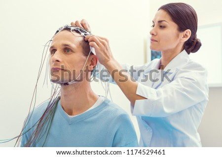 Finishing touches. Female laboratory worker fixing electrodes before examining her male patient brain on an electroencephalography machine. #1174529461