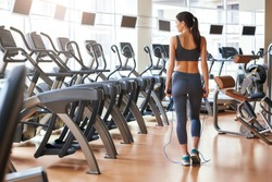 Finishing workout. Back view of short and slim young woman in sportswear standing at gym with jump rope