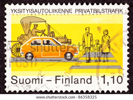 FINLAND - CIRCA 1979:  A stamp printed in Finland noting traffic safety shows family of three crossing a street at a crosswalk while two cars, a modern subcompact and a Model-T, wait, circa 1979.
