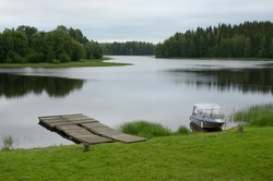 Finland river landscape with woody pier and powerboat
