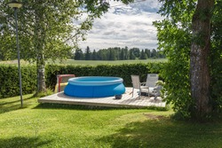 Finnish country house yard. Playground. Children's playhouse. Inflatable pool in the yard.