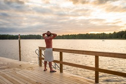 Finnish sauna. Sunset on the lake. Wooden bathhouse or sauna with descent into the water. A man in a special hat for a bath is wrapped in a towel. He looks at the sunset and raises his hands up.