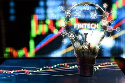 Fintech Investment Financial Internet Technology Concept. Light bulb on tablet and Stock graph and business technology icon with abstract electronic circuit background