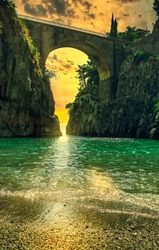 Fiordo di Furore, Amalfi coast picturesque golden hour sunset seascape scenic view on arched bridge between high rocks and stone beach and turquoise clear Tyrrhenian sea on Summer day, Italy, Campania