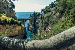 Fiordo di Furore, Amalfi, panoramic scenic aerial view on arched bridge between rocks of fjord, long stone staircase leading to beach and bay, clear blue Tyrrhenian sea. Italy, Campania, Amalfi coast.