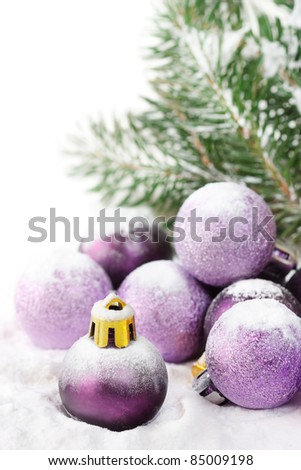 Fir and purple christmas baubles with snow.