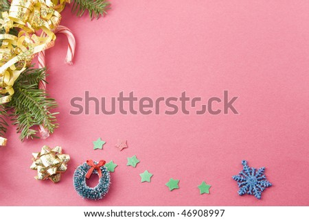 fir branch, gold foil bow, candycane, wreath and stars on textured red background