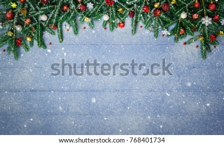 Fir Branches and Christmas Ornament on snowy blue wood plank. #768401734