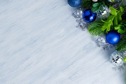 Fir branches with blue Christmas balls and decor are spread out on a gray background. Postcard with space for writing text.