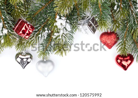 Fir tree branch with christmas decor covered with snow. Isolated on white background