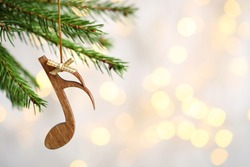 Fir tree branch with wooden note against blurred lights, space for text. Christmas music