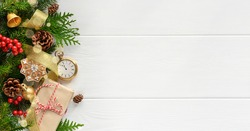 Fir tree branches with Retro style clock christmas decorations and gift on white wooden background. Last moments before Christmas or New Year. New Year's Eve. Top view. Copy space
