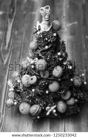 Fir tree decorated with nuts, dry anise and acorns. Christmas tree model made of grape branches. Christmas decorations concept. Cones and dried fruits on little tree on wooden background #1250233042