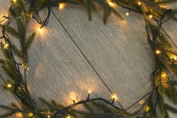 Fir tree garland with flash lights as a frame on wooden background