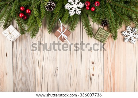 Fir tree with christmas decorations and gift boxes on wooden background #336007736