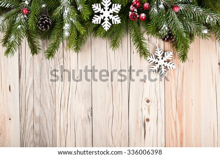 Fir tree with christmas decorations on wooden background #336006398