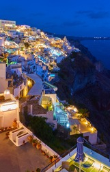 Fira town in Santorini island at dusk, Greece. Night landscape with  brightly lit city on the coast