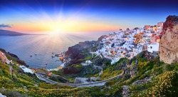 Fira town on Santorini island, Greece. Incredibly romantic sunset. Oia village in the morning light. Amazing sunset view with white houses. Island lovers. Panorama of the bay. Santorini flowers.