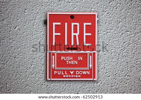 Fire alarm button on concrete wall background.