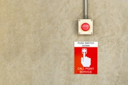 fire alarm call point service sign label with red color push button switch on cement wall.