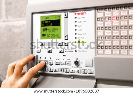 Fire alarm control panel is activated and in alert mode. Display message: Alarm active hall smoke. Red flickering lights and peeping. A hand is using the silence button. Selective focus. Photo stock ©
