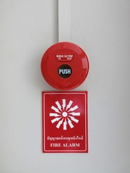 Fire Alarm Equipment. Red manual call point for Fire alarm on the wall with label description (with Thai text) and icon symbol.