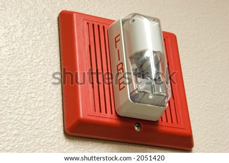 Fire alarm light and siren hanging on wall.