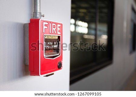 Fire alarm switch on the factory wall.