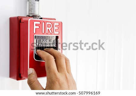 Fire alarm switch,The hand of man is pulling fire alarm on the wall next to the door,Fire alarm switch.Break glass and press button to activate. With hand and direction arrow,