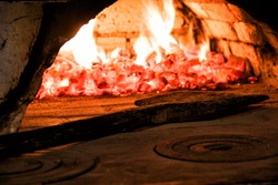 Fire and fire in an old oven and a wooden shovel