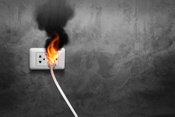 fire and smoke on electric wire plug in indoor, electric short circuit causing fire on plug socket.
