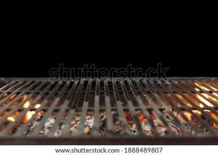 Fire Barbecue Grill Isolated On Black Background. BBQ Flaming Grill Background Isolated. Hot Barbeque Charcoal Cast Iron Grill With Bright Flames In Perspective View.