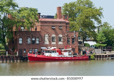 Fire Boat on the River A boat equipped for fire fighting is docked at a brick fire station on the Cuyahoga River in Cleveland, Ohio