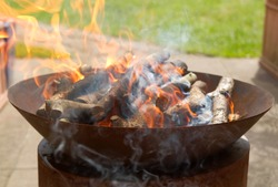 Fire bowl with burning wood in the garden