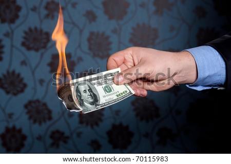 Fire burn one hundred dollars in  hand