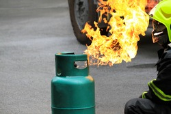 Fire burning on green gas container. and Firefighter or fireman in black uniform and wearing safety helmet try to extinguish the fire on street with car wheel background and copy space. Conflagration