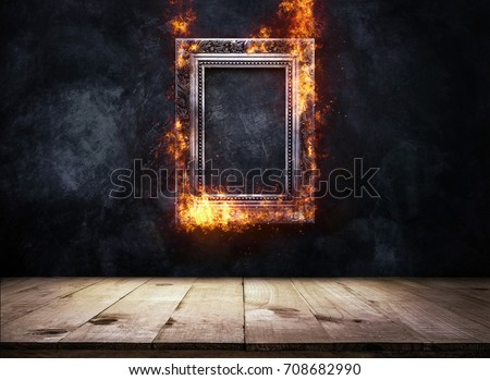 Fire Burning silver Antique picture Frame on dark grunge wall with Wooden table top, Empty ready for product display or montage.