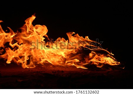 Photo of  Fire burns, waving back and forth by the wind at night on a black / yellow-red background. Heat energy
