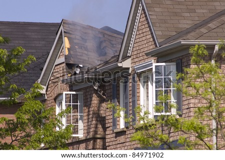 Fire damaged smoldering roof of a nondescript brick house. - stock photo