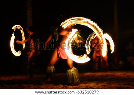 Fire dancers at Hawaii luau show, polynesian hula dance men juggling with fire torches.